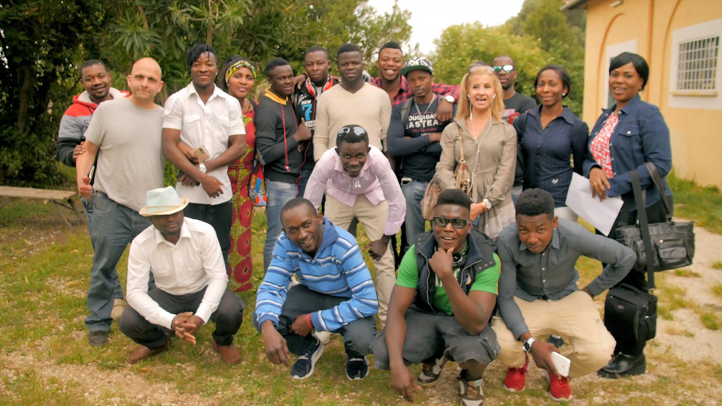 Marie-Christine (4th from the left at the back) with refugees and charity workers in Italy
