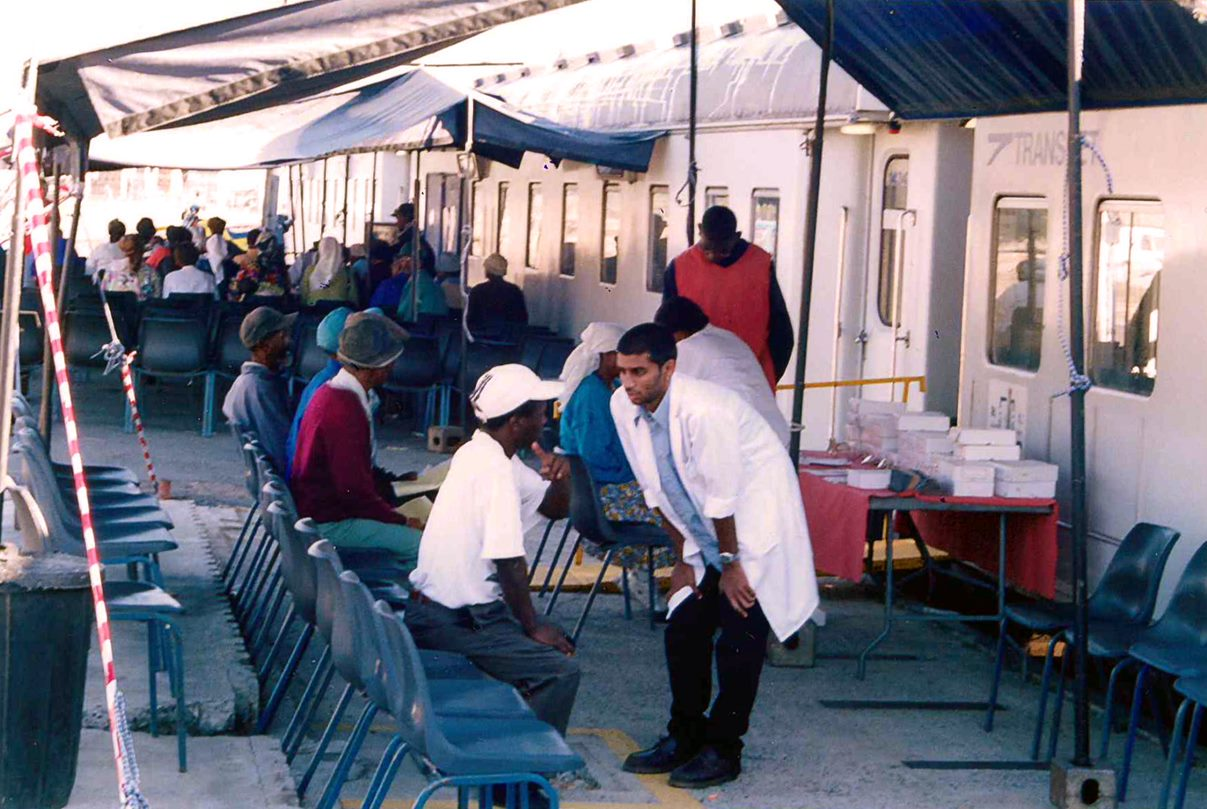 An optometry student consults with a patient at the Phelophepa train