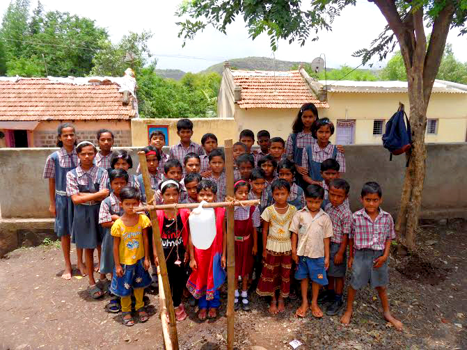 School children with the tippy tap handwashing device